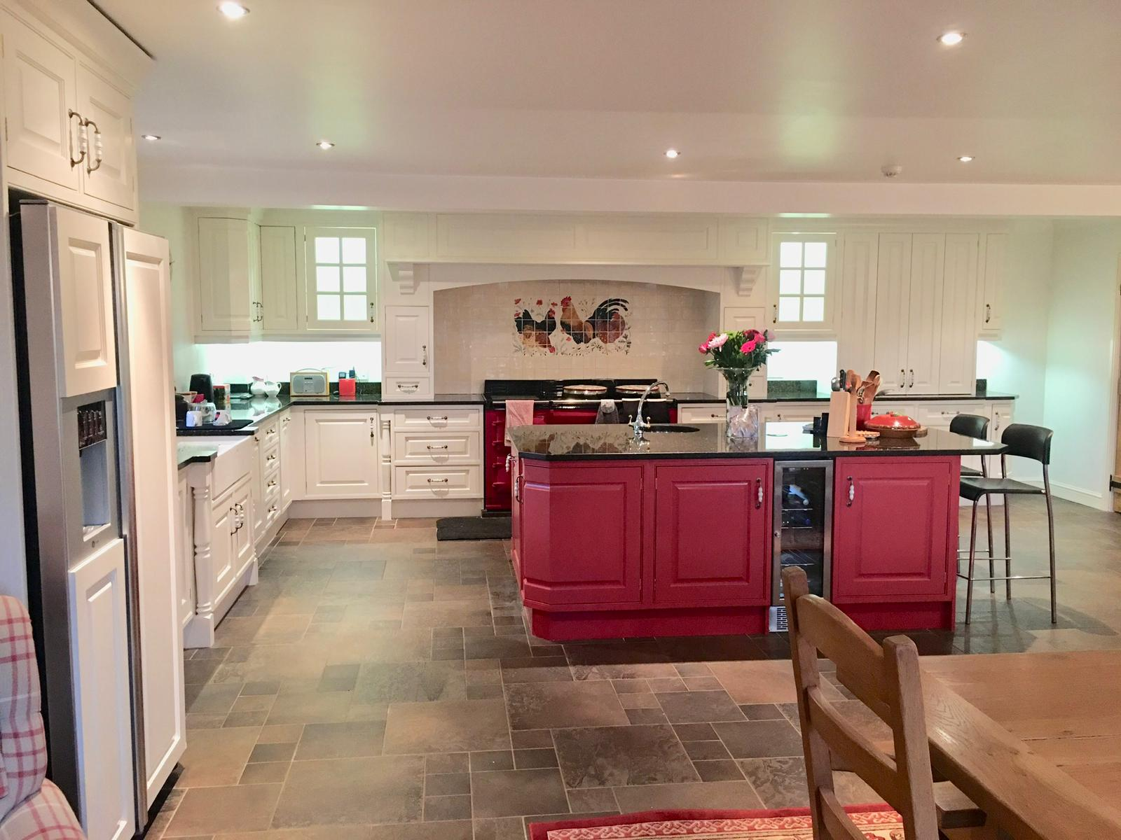 Large bespoke kitchen hand painted in Farrow and Ball pointing on the main cabinets and Farrow and Ball Radicchio Red on the island